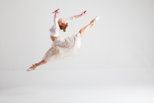 開脚して跳んでバレエを踊る白人女性