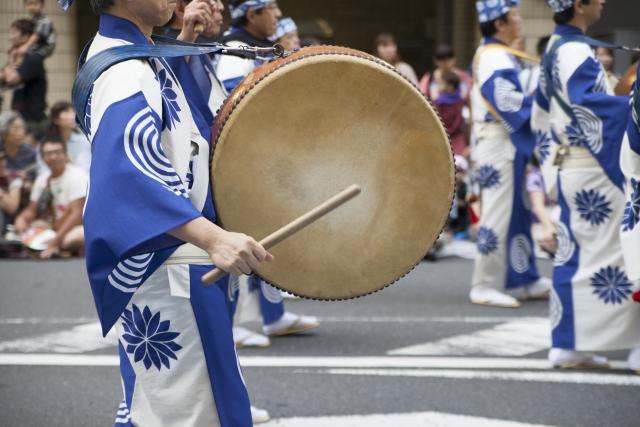 阿波踊りで太鼓を叩いて歩く男性