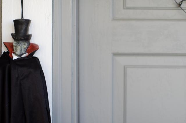 ドアのどばに立つドラキュラに仮装した男性