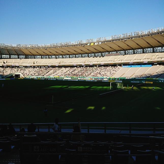味の素スタジアムの日光が当たる席でサッカー観戦する人たち
