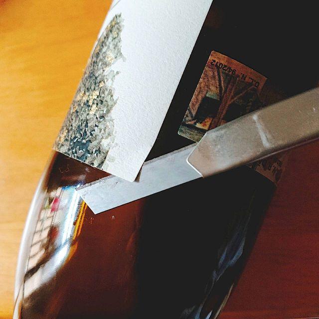 ワインのエチケットをカッターを使って剥がしていくところ